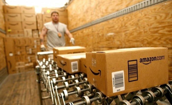 Un trabajador de amazon manipulando cajas con envíos de Amazon