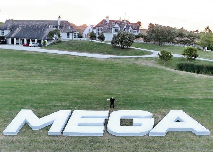 Dotcom en su casa frente a las letras de Mega