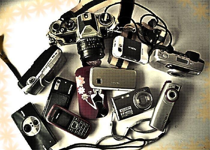 Varias cámara y móviles amontonados