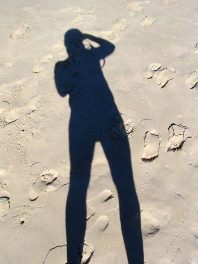 Sombra sobre arena de una persona que se retrata a sí misma