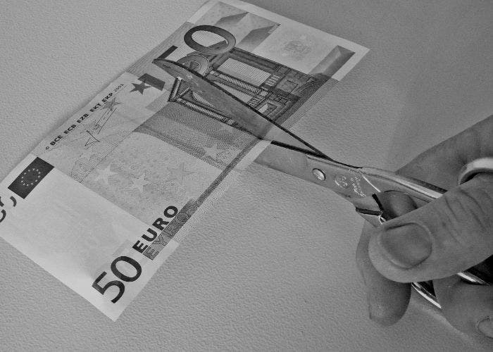 Cortando un billete con unas tijeras