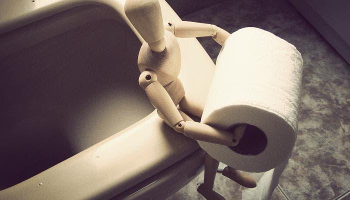Váter con un muñeco sujetando el papel higiénico