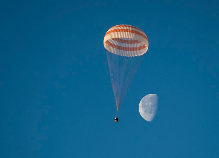 Descenso de la cápsula Soyuz en paracaídas, con la Luna al fondo