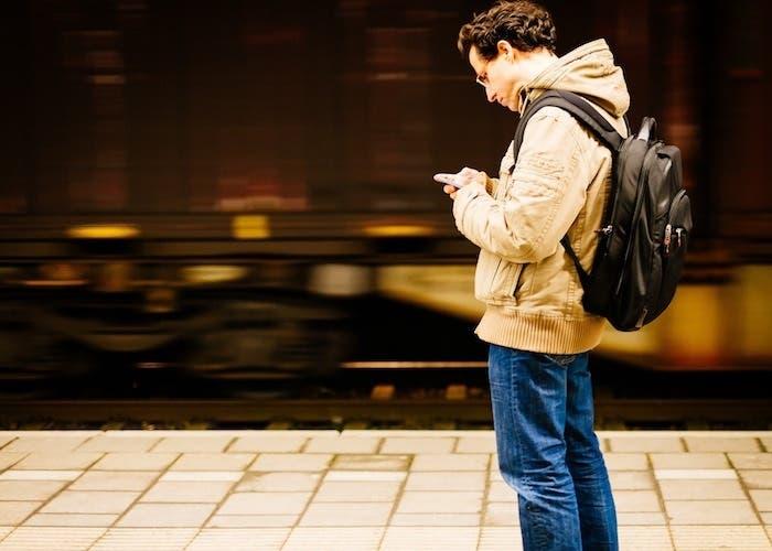 Viajero usando internet en estación tren