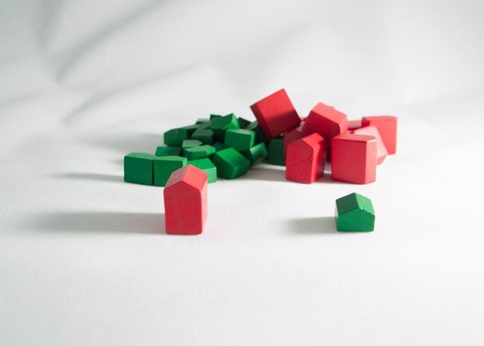 Casas y hoteles del Monopoly amontonados tras dos bien puestas